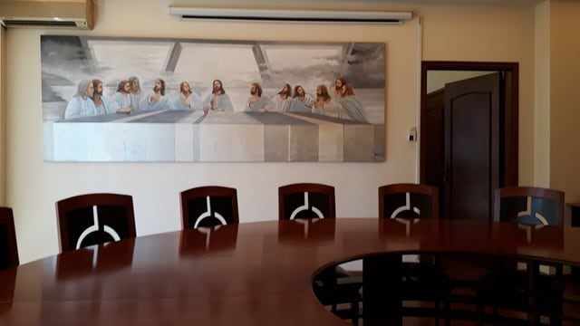 """Ein Konferenztisch mit mehreren Stühlen, dahinter ein Bild des """"letzten Abendmahls""""."""
