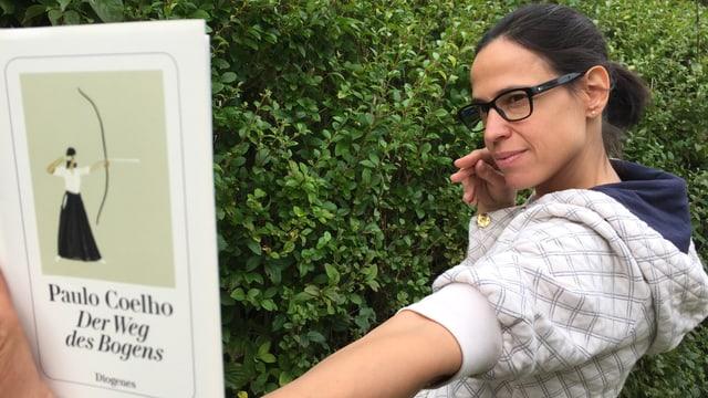 Annette König hält das Buch  «Der Weg des Bogens» von Paulo Coelho wie eine Bogenschützin in der Hand