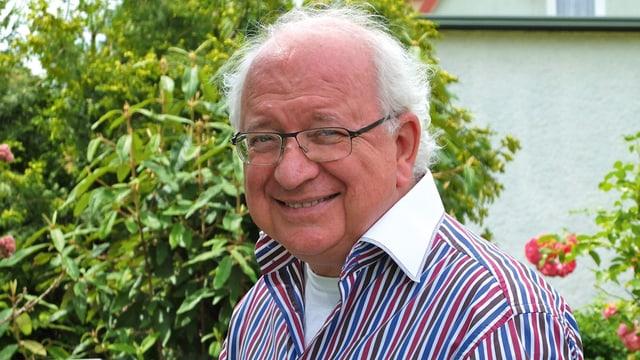 Ein älterer Herr mit Brille im gestreiften Hemd in seinem Garten.