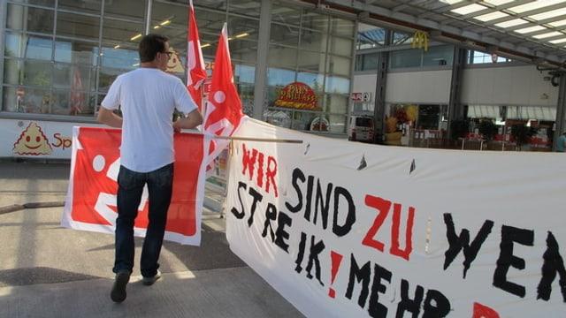 Unia-Mitarbeiter rollt Transparente der Unia ein und versorgt Fahnen der Gewerkschaft. Er trägt ein weisses T-Shirt und schwarze Hosen, und trägt eine Brille.