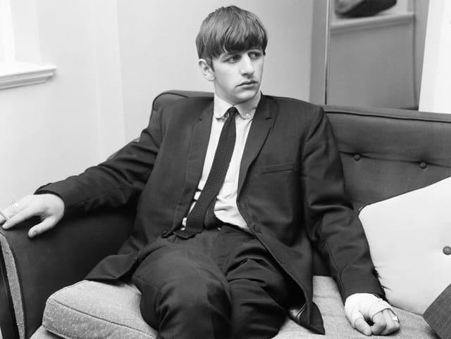 Portrait des jungen Ringo Starr. Schwarz-weiss-Aufnahme, wie er auf einem Sofa sitzt. Er trägt einen Anzug.