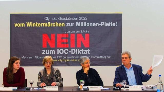 Drei Frauen und ein Mann sitzen vor einem Plakat an einer Pressekonferenz