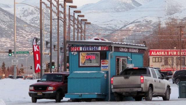 Zwei Pick-Up-Trucks, dazwischen ein Kiosk.