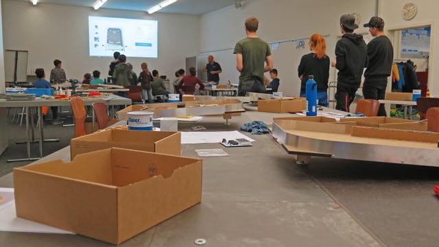 Gruppenraum mit Kartonschachteln im Vordergrund und jungen Menschen im Hintergrund.
