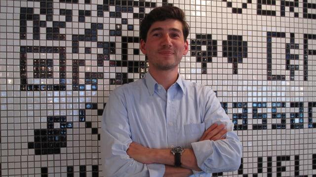 Ein junger Mann steht mit verschränkten Armen vor einer schwarz-weiss gekachelten Wand