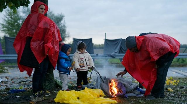 Eine Flüchtlingsfamilie wärmt sich am Feuer auf