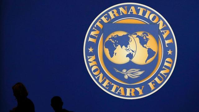 Personen gehen am IWF-Logo vorbei