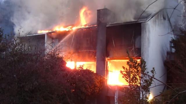 Flammen schiessen aus den Fenstern eines Einfamilienhauses.