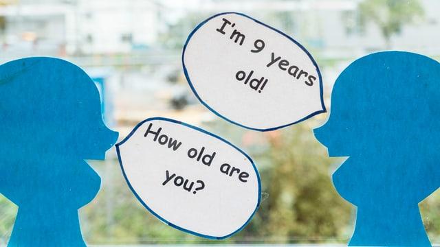 Zwei Kinderköpfe mit englischen Sprechblasen