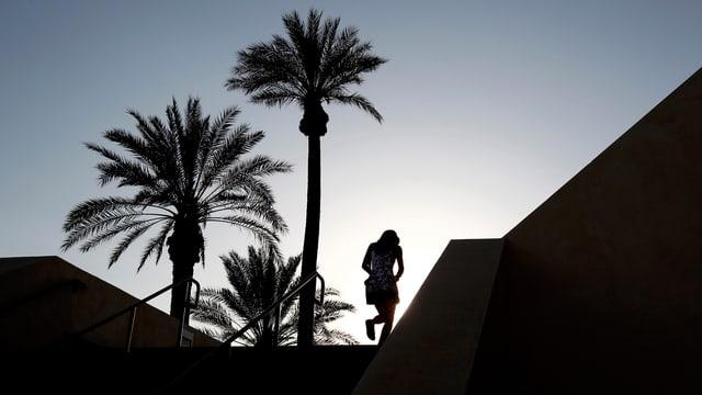 Ein Mädchen geht neben Palmen eine Treppe hoch.