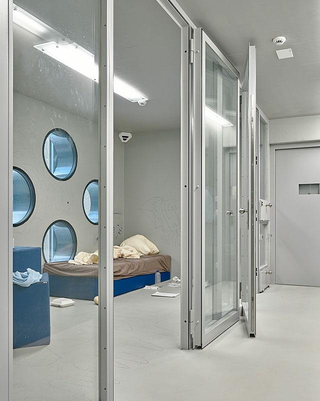 Eine Gefängniszelle hinter Glastüren.