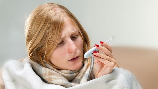 Kranke Frau schaut auf Fieber-Thermometer