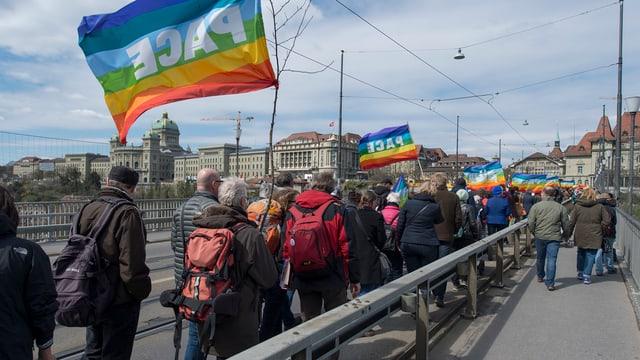 Glieud cun bandieras Pace chaminan, davos bajetgs vegls da Berna.