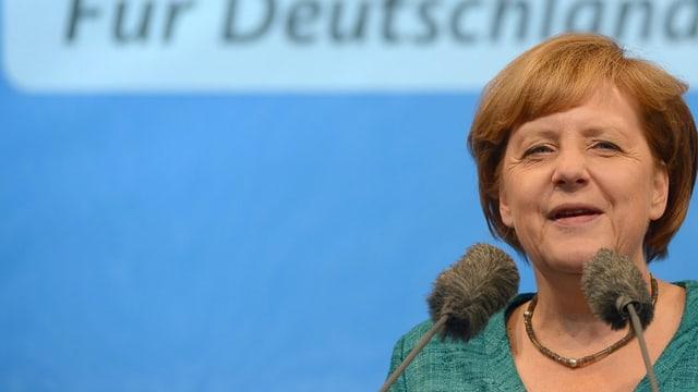 Angela Merkel vor dem Mikrofon, in grünem Pullover vor blauem Hintergrund, auf dem 'Für Deutschland' steht.