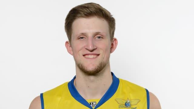 Junger Mann mit blondem Haar und Bart sowie gelbem Sporttrikot