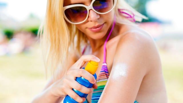 Eine Frau im Bikini sprüht Sonnenschutz auf ihren Oberarm.