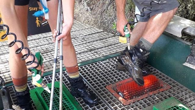 Zwei Wanderer mit nackten Beinen spirtzen ihre Schuhe ab.