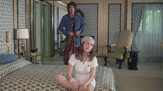 Ein junges Mädchen sitzt auf dem Bett und im Hintergrund nähert sich ein junger Mann.