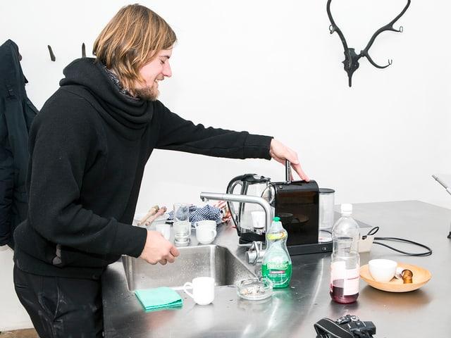 Ein Mann steht in einer Küche und bedient eine Kaffeemaschine