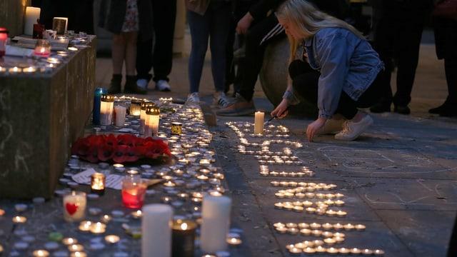 Eine junge Frau zündet Kerzen an.