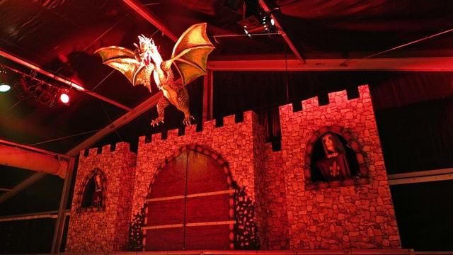 Bühnenbild aus Burg mit lebensechtem Drachen aus Pappmaché im Scheinwerferlicht