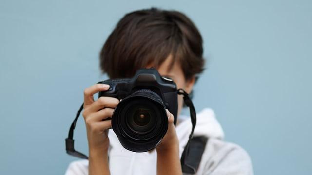 Frau fotograrfiert mit einer Spiegelreflexkamera.