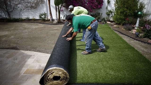 Arbeiter rollen Kunstrasen im Garten aus