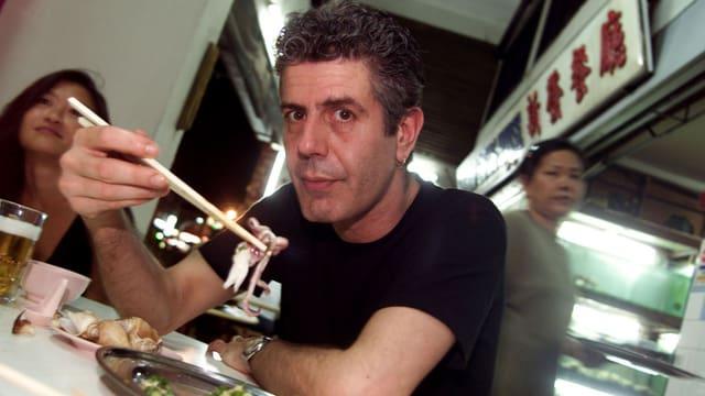 Anthony Bourdain isst mit Stäbchen.