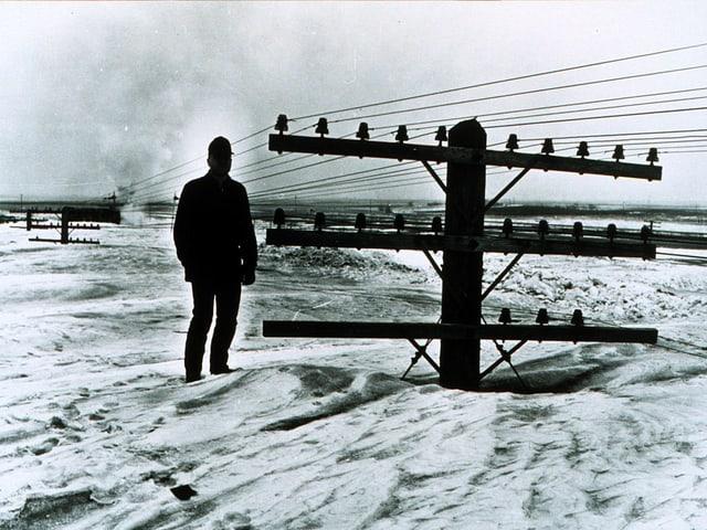 Auf einem alten Bild sieht man einen Mann auf meterhohem Schneee stehen. Neben ihm ragt nur noch die Spitze eines Strommasten heraus.