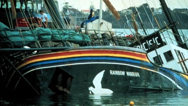 Ein Schiff liegt in Schräglage halb geflutet im Wasser. Auf der Bordwand ist ein Regenbogen und eine weisse Taube zu sehen.