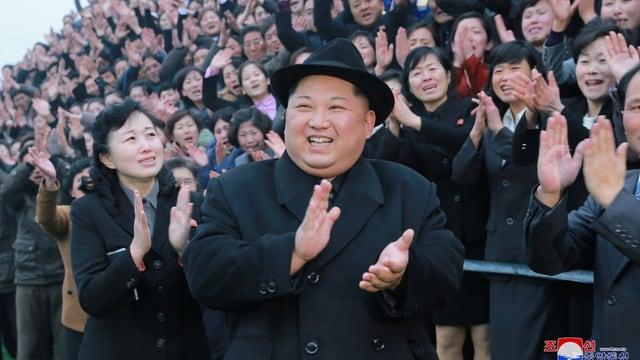 Kim in schwarzem Mantel mit Hut klatscht und lacht vor einer begeisterten Menschenmenge.