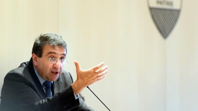 Pascal Broulis spricht sitzend am Mikrofon im Hintergrund das Waadtländer Wappen.