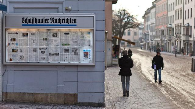Eine Zeitungsausgabe im Schaufenster eines Hauses. Nebenan eine Strasse und eine Häuserzeile.