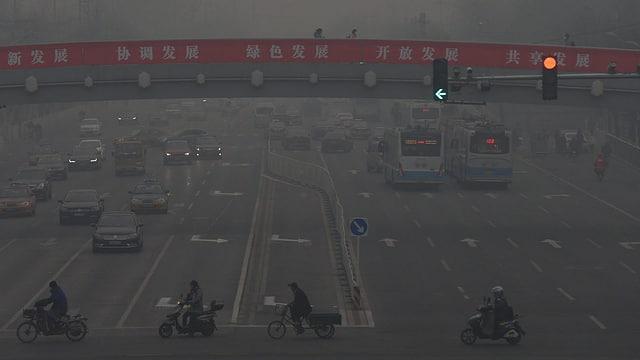Autos und Motorräder in dichtem Smog in Peking.