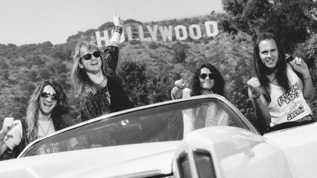 """Schwarzweissfoto: Vier Männer mit langen Haaren und Sonnenbrillen posieren in einem Cabrio vor dem """"Hollywood""""-Schild."""