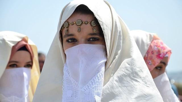 Eine Frau mit hellem Schleier, mit extra Mundschutz und Stirnschmuck.
