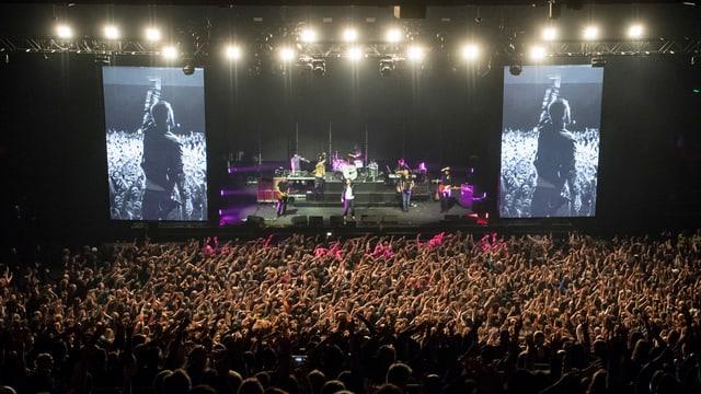 Veranstaltungshalle mit Publikum, Musikband und zwei Bildschirmen