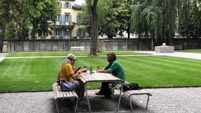 Drei Menschen sitzen an einem Tisch im Park und trinken Bier.