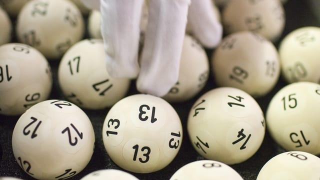 Eine Hand in Handschuhen greift nach Lottozahlen.