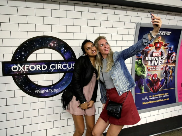 Zwei Frauen machen in der U-Bahnstation ein Selfie.