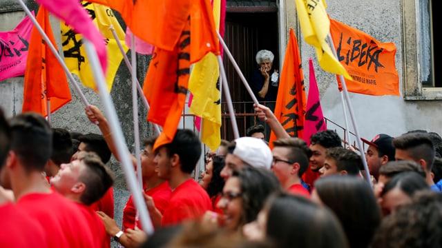 Demonstranten schwingen farbige Fahnen der Antimafia-Organisation Libera.