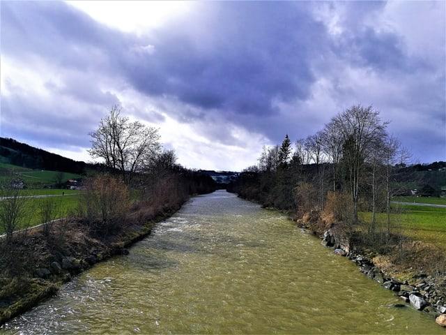 Ein kleiner Fluss, am Ufer  Bäume, der Himmel ist teils mit Wolken überzogen.