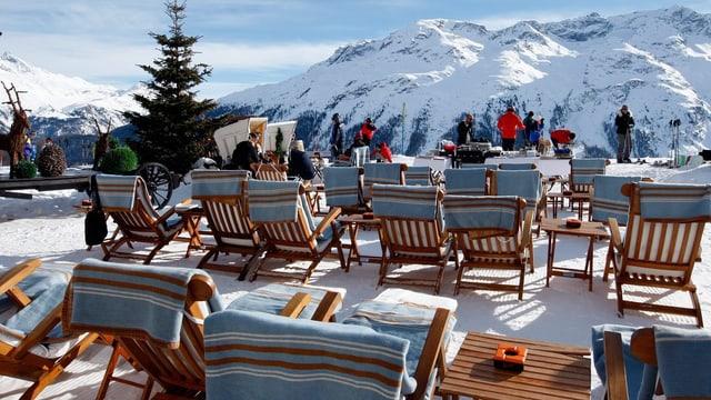 Eine Terasse mit Liegestühlen und Bergpanorama.