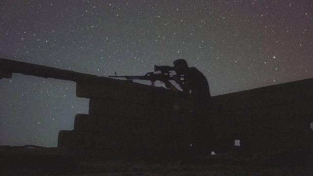 Eine Aufnahme im Dunkeln von einem Mann, der in einer Festung steht und eine Waffe hält.