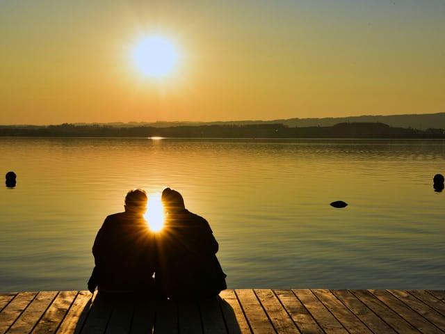 Ein paar am Seeufer bei Sonnenuntergang.
