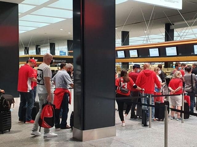 Lange Schlange vor dem Check-in Schalter am Flughafen Zürich.