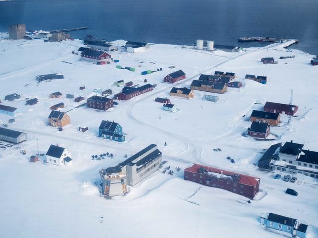 Häuser auf einer mit Schnee bedeckten Landschaft in der Arktis.