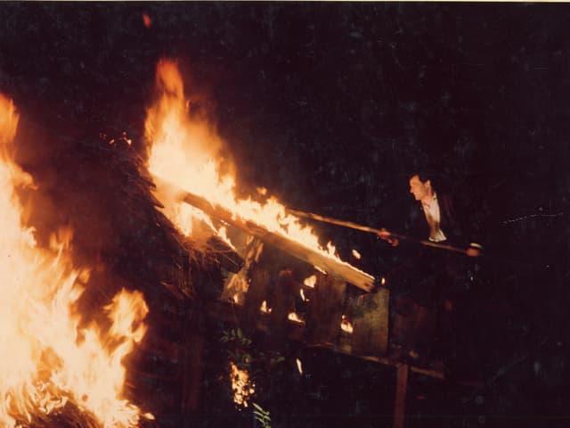 Christen stochert mit einer Bohnenstange im Feuer eines Hauses.