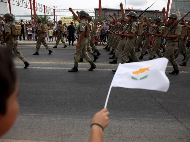 Ein Junge schwenkt eine zypriotische Fahne an einer Militärparade.