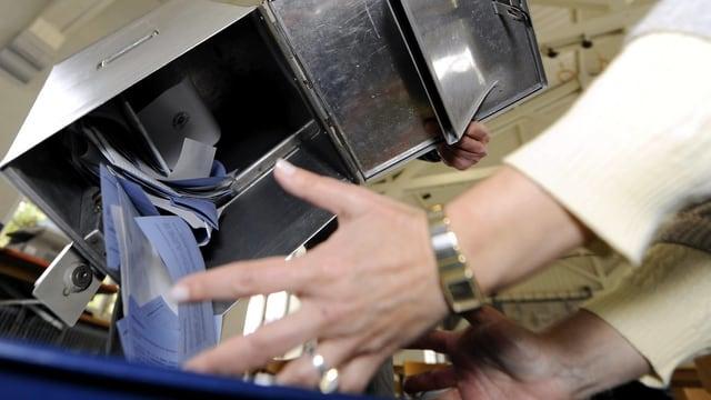 Zahlreiche Stimmzettel fallen aus einer Urne in die Hände einer Stimmenzählerin.